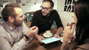 incontro di lavoro nella caffetteria. il team sta utilizzando il tablet