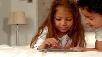 crianças hispânicas brincando juntas em um tablet