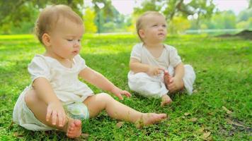 Caucasian girl jumeaux trottiner ensemble dans le jardin