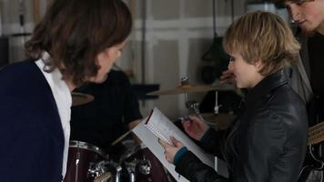 Band members work together writing song lyrics video