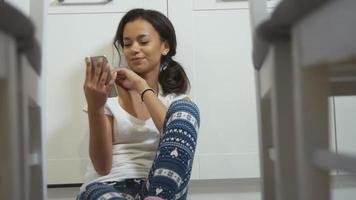 hübsche junge afroamerikanische Frau, die in einem Küchenboden sitzt und auf Handy schreibt.