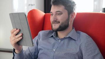giovane uomo seduto in poltrona rossa