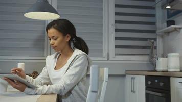 bela jovem afro-americana usando um computador tablet em uma cozinha.