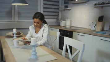 belle jeune femme afro-américaine à l'aide d'un ordinateur tablette dans une cuisine.