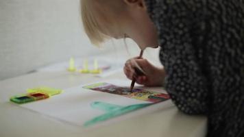 une petite fille dessinant une maison avec un crayon. ralenti.