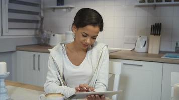 bella giovane donna afroamericana utilizzando un computer tablet in una cucina.