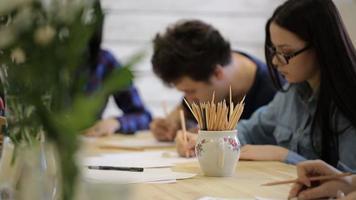um grupo de rapazes e moças sentados à mesa fazendo cursos de desenho video