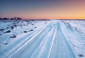 traces of the car wheels on a snowy road photo