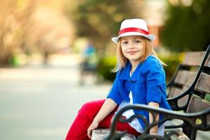 Portrait of little girl on bench in a park