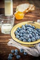 Gardening blueberries in a simple rustic bowl on dark wooden