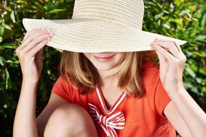 Happy girl with hat in summer garden