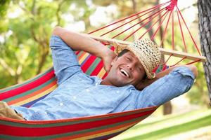 Smiling man relaxing in a colorful hammock