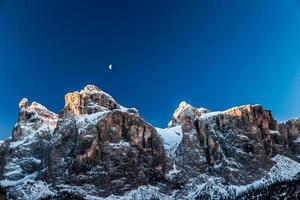the moon is shining behind a peak photo