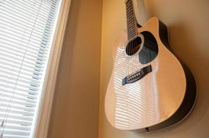 Acoustic guitar hanging on the wall close up
