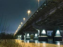 Bridge above water with lights at night