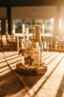 Tres botellas de vidrio transparente sobre mesa marrón