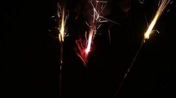 Three Sparklers Burning Together Against Dark Background video