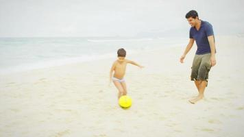 Family plays soccer together on a beach