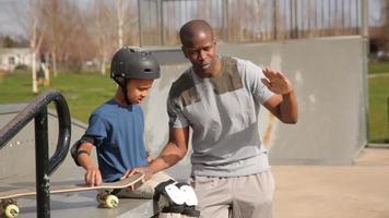 vader en zoon samen bij skateboardpark