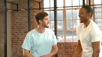 adapter les gens souriant ensemble dans la salle de gym