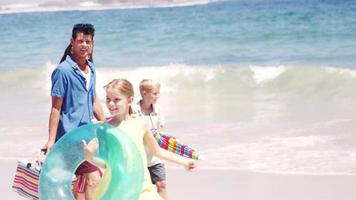 família jovem caminhando junto com coisas de piquenique
