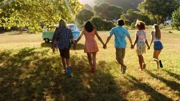grupo de amigos de mãos dadas e caminhando juntos