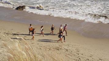 Groupe de jeunes marchant ensemble le long de la plage