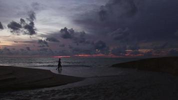 um casal caminhando juntos na praia, ao pôr do sol.