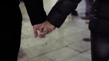Couple hands closed together outdoors. Hand-in-hand