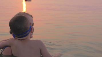 mãe e filho nadando no mar juntos