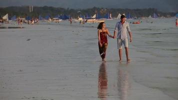 pareja caminar juntos por la playa al atardecer video