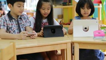 .Asian child playing together with a computer tablet .