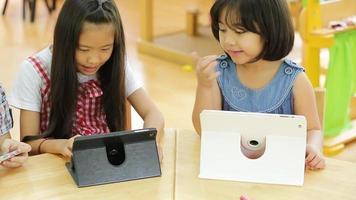 .asian criança brincando com um tablet de computador.