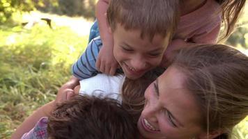 Niños y padres jóvenes divirtiéndose juntos al aire libre