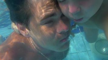 pai e filho mergulhando juntos na piscina