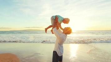 pai filho brincando juntos ao pôr do sol na praia.