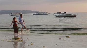 casal caminha junto na praia ao pôr do sol