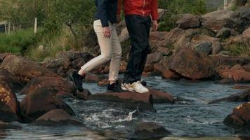 Paar überquert gemeinsam einen Bach auf dem Land video
