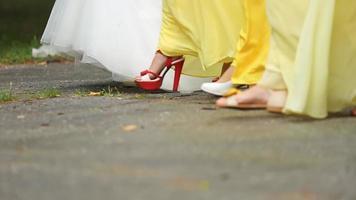 La novia y sus damas de honor caminan juntas sobre el asfalto.