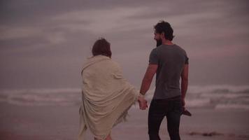casal de mãos dadas enquanto caminham juntos na praia