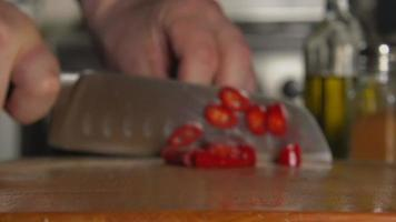 SLOW: A cook's hand cuts a chili pepper by a knife