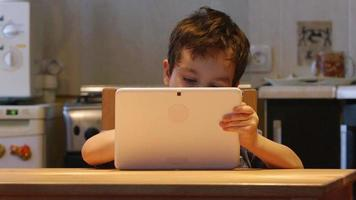 A cute little child holds at hands a tablet PC at a table