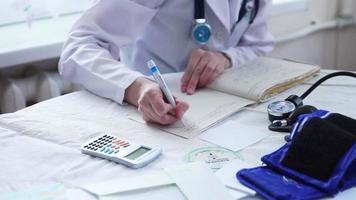 mani del medico in uniforme bianca prescrizione di scrittura a un paziente