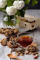 Cup of tea and cookies made of nuts and raisins. photo