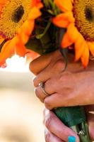 Woman holding bouquet with wedding ring photo