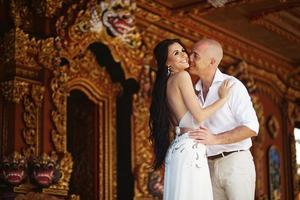 Bride and groom kissing against balinese temple