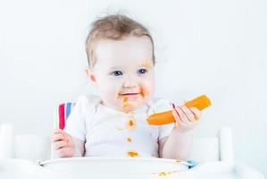 Cute baby eating her first carrot