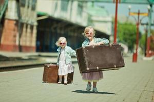 Vintage looking picture of small girls with luggage