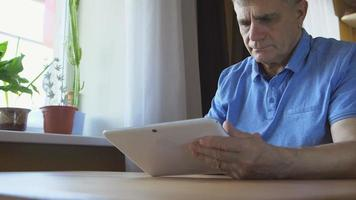 Aged male sits and uses a tablet PC at home
