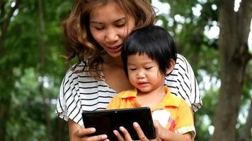 Asian boy and mother are playing game on tablet together at the park. video